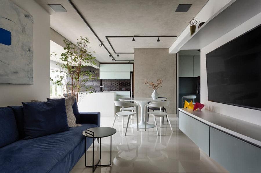 白い艶のあるタイルに白いチェアと丸いダイニングテーブルでコーディネートしています。アクセントにブルーのソファーがものすごく強調しています。キッチンの壁面にも石を使っていて高級感のある空間です。部屋自体はそこまで広くないのですがリビングテーブルで小さいテーブルを配置していることで圧迫感を軽減しています。