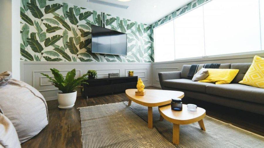 ダークブラウンからのフローリングにテレビ台はブラックです。壁紙はかなり個性的なものを使用しています。テレビは壁掛けテレビになっています。クッションが黄色でアクセントになっています。