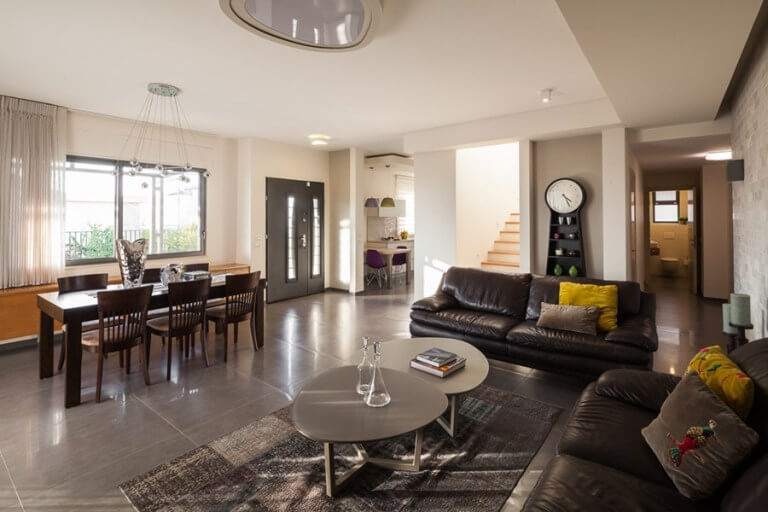 こちらのタイルは1枚がかなり大きいタイルです。ソファーや家具はダークブラウンカラーを使用しています。クッションのイエローでアクセントを設けています。