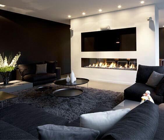 明るいフローリングにダークグレーのコーナーソファーで白い壁に暖炉が埋め込まれています。暖炉の上にテレビが埋め込まれていてとてもすっきりした印象です。テレビは暖炉の熱で壊れないのか心配ですが。