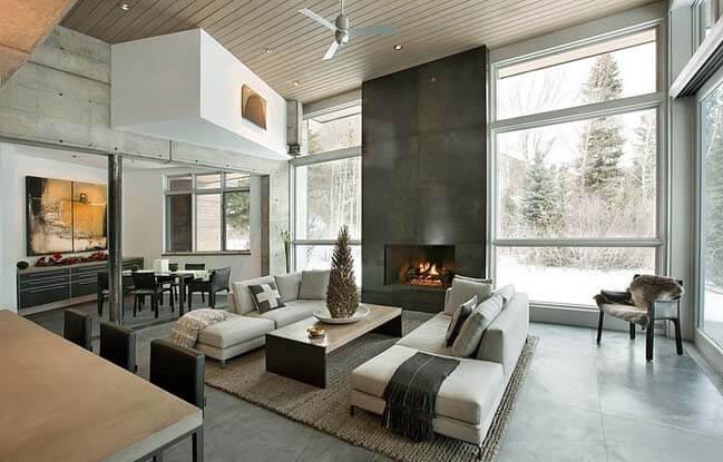 中立的な色とコンクリートのグレースケールの特性を持つこの美しい家は、雪で覆われた松の木の中にあります。寒さとシンプルな外見とは対照的に、インテリアは非常に居心地が良く、自然光で満たされています。あなたは暖かい歓迎の家として近代的な暖炉とキッチンとリビングルームのオープンスペースを参照してください内に入る