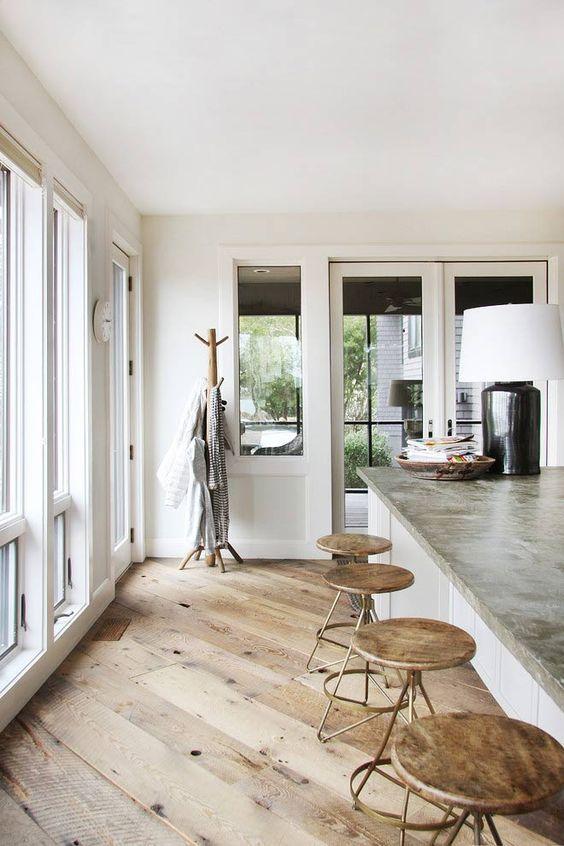ライトブラウンからのフローリングでキッチンの天板が石を使用しています。バースツールとコートハンガーがミディアムブラウンカラーで統一されています。
