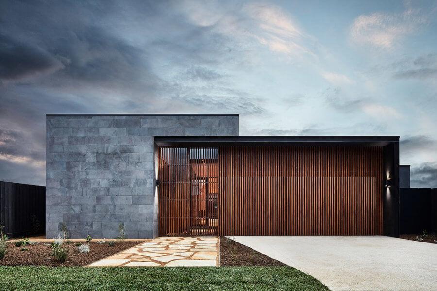ブルーストーンと天然の硬材を混ぜたクラッドで、家は中央の芝生を包みます。床から天井までの窓は、室内と屋外の間を直結しています。中庭も視覚的には存在しますが、窓ガラスが開き、居間を芝生のテラスに広げます。