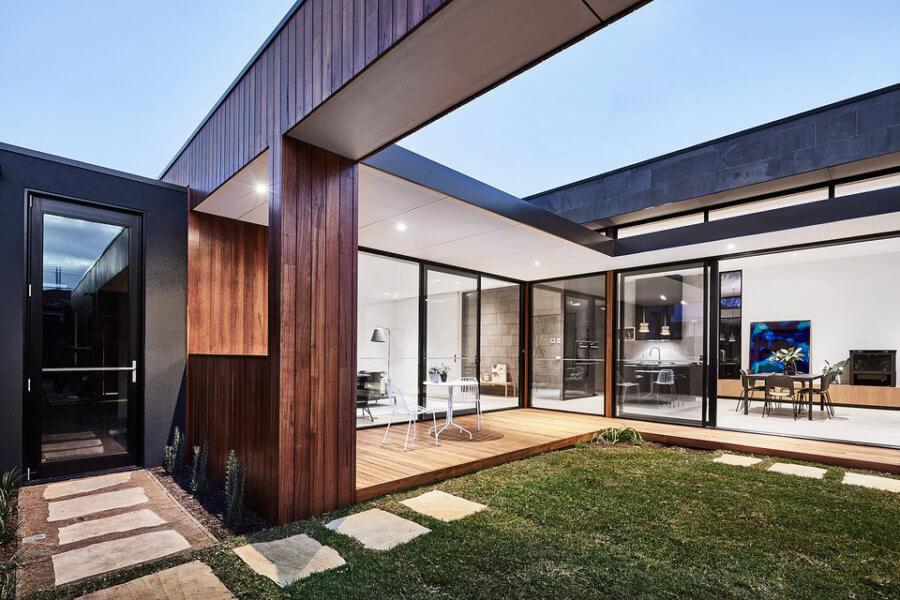 自然光がマットな黒いキッチン、真鍮の仕上げ、ワイドなオーク材の床で作られたモダンなインテリアを洗います。