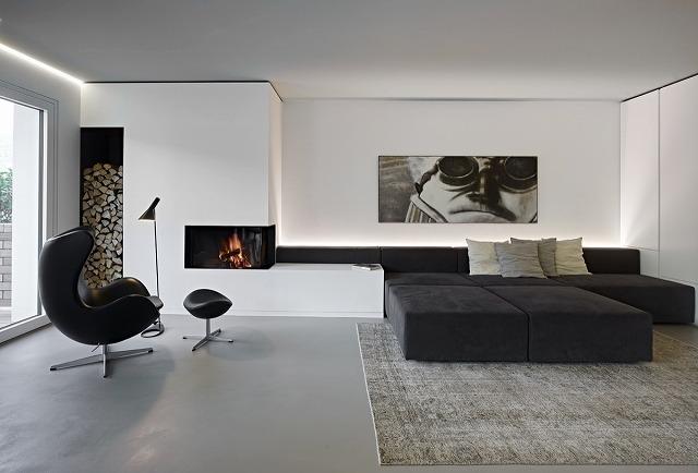 ここでは、単色のリビングルームが豪華な快適さを醸し出しています。快適な読書用の椅子と高級なソファーが、くつろいでリラックスするのに最適な場所です。暖炉と積み重ねられた薪は、それがシックであるほど豊かです。