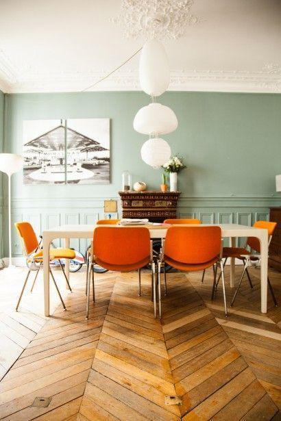 壁面の色は淡いグリーンでダイニングチェアの色はオレンジ色です。アクセントカラーを2色使っていますがデザインがシンプルなので北欧特有のインテリアが出来上がっています。フローリングは使い込まれた木材を使用しています。