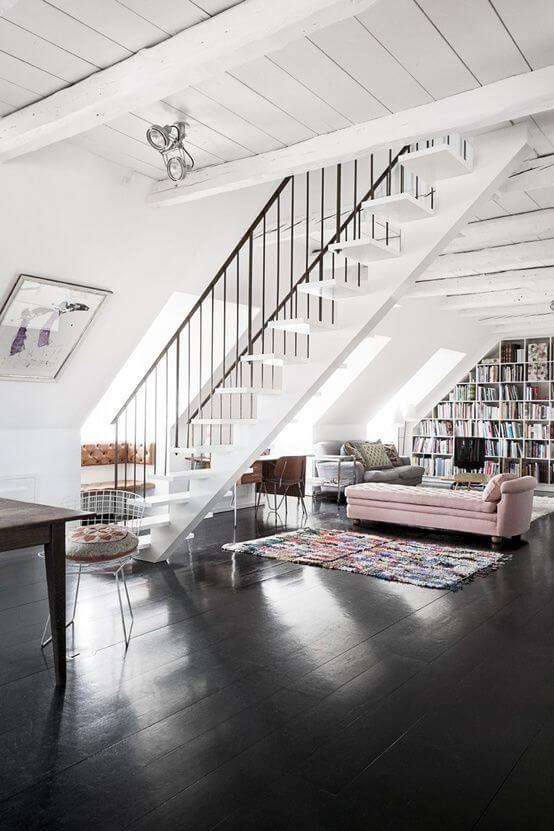 床がブラックでピンク色のカウチソファを配置してカジュアル感を演出した海外事例