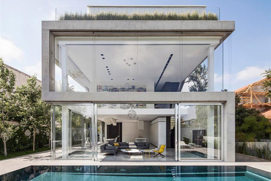 Pitsou Kedem Architectsのコンクリートカットハウスは、3つの直角プリズムが積み重ねられた形をしており、コンクリートの連続線から作られているかのように見えます。2階建てのメイン・リビング・スペースはガラスパネルで囲まれており、庭園やプールエリアに自然に流れるようになっています。