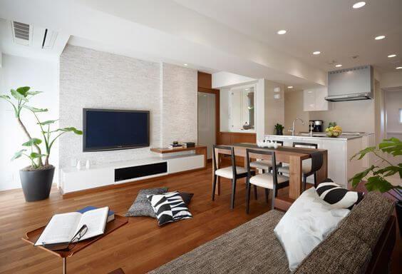 フローリングの色はミディアムブラウンです。ホワイトとバランスよく色配分しています。テレビは壁掛けテレビで背面は石を使っています。キッチンはオープンキッチンです。レンジフードがよく見えるのが最近の特徴ですね。