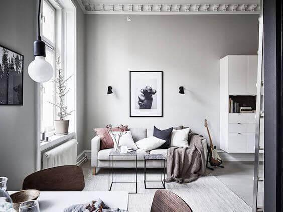 白いフローリングに白い家具を合わせています。クッションはネイビーとピンク色を使っています。さりげなくギターがソファーの横に置いてあります。ダイニングチェアは木のぬくもりのあるものです。