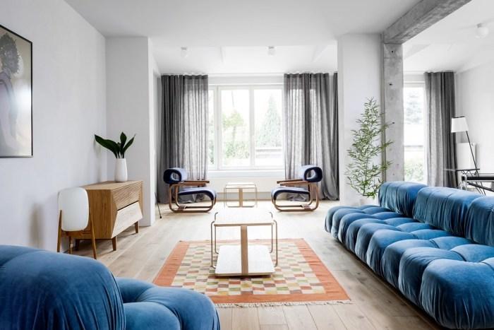 ホワイトに近いフローリングで鮮やかなブルーのソファーを配置してコーディネートしています。木製家具はナチュラルカラーで全体的に優しい印象を与えています。