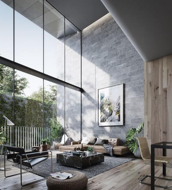 明るいフローリングでそのまま同じ木材で壁面にも取り付けており一体感を醸し出しています。一部は石の壁面になっていてラグマットのグレーと色が合わさっています。ガラス張りの窓もものすごく広く高さも充分です。日差しがたくさん入り昼間は照明が必要ないでしょう。