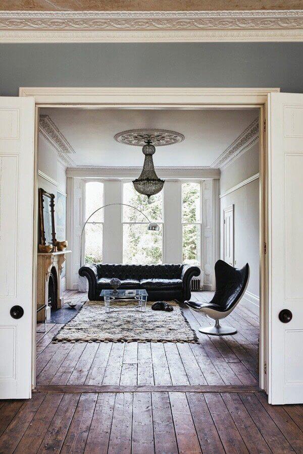 古材の床に扉があり奥にクラシックなソファが置いてあります。窓からは緑が見えて自然光がたくさん降り注ぎます。