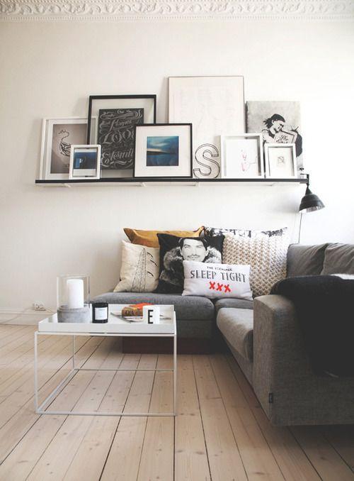 ホワイトに近いフローリングでグレーのコーナーソファーをレイアウトしています。壁面に店を設けてその上に絵や写真をたくさん飾っています。デッドスペースがうまく使われていますね。海外の住宅は石でできているので壁面に店をつけやすい状態です。日本の在来工法では心材が全ての面に入っているわけではないので難しいです。