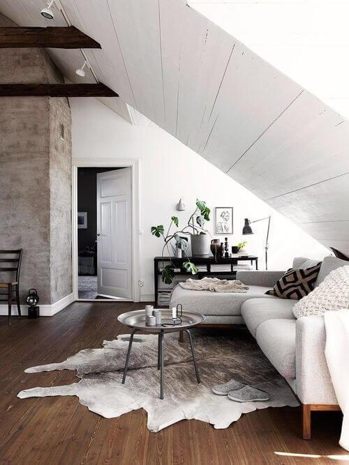 フローリングの色はミディアムブラウンからです。カウハイドのラグを使用しています。天井が斜めに降りてきているので圧迫感を感じてしまいますのでソファーは明るい色で軽減しています。