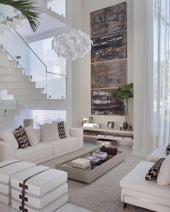 白いタイルに白いソファーで吹き抜けがものすごく高い空間です。おそらくかなりの工程だと思われます。インテリアアートでアクセントカラーを教えています。ギザギザのクッションがいい感じでアクセントになっています。