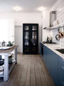 使い込まれた古い床材にブルーのキッチンが映えるビンテージとモダンが融合したミックススタイルのインテリア事例