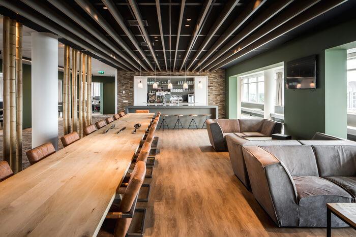 作業場所は、魅力的な緑色の柱と、空間的な雰囲気のための昼光が豊富な快適なスツールを備えたステーテーブルを繰り返し建築した半オープンギャラリーとして設計されています。