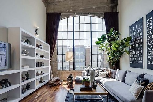 建物はコンクリートの打ちっぱなしを使っていて新しい建物ではないと思われます。壁はホワイトでリフォームできれいになられていてソファーはライトグレーのコーナーソファーを配置しています。観葉植物がかなり背の高いものを置いて空間の天井の高さをアピールしています。個人的にお気に入りのインテリアです。