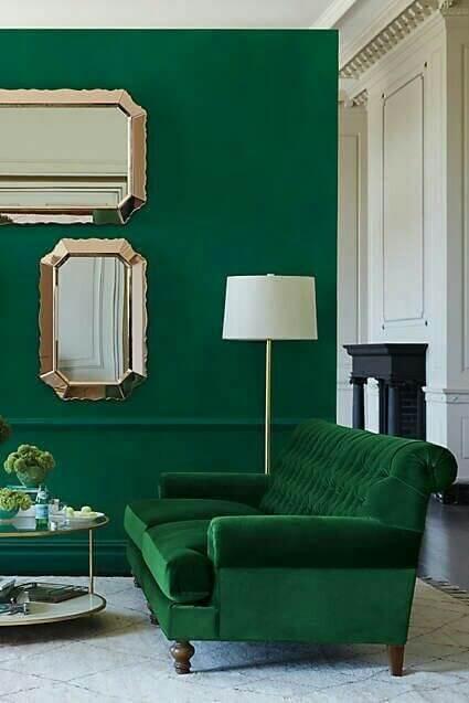 グリーンの壁とソファのややクラシカルな印象のインテリアの画像