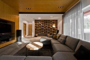 まだ家の居間には、木製の棚の壁に暗い色が塗られ、この棚の裏側にコントラストが描かれています。この環境を完成させるために、黒のアームチェアが置かれ、その隣にランプがあり、読書に最適です。