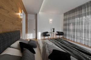 既に家の親密なエリアにあるマスターベッドルームにはダブルベッドの棚を兼ねる木製の壁があります。ベッドは明るい灰色の色合いを持つカーテンに合った、灰色の濃淡で、多かれ少なかれ暗いです。