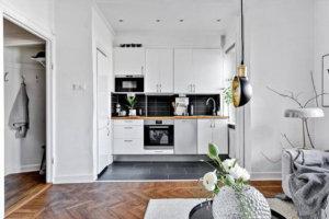 ヘリンボーンの古材の床とキッチンが見えるイメージ キッチンがホワイトですがカウンター部分だけナチュラルカラーで床の色と揃っているのがおしゃれです。