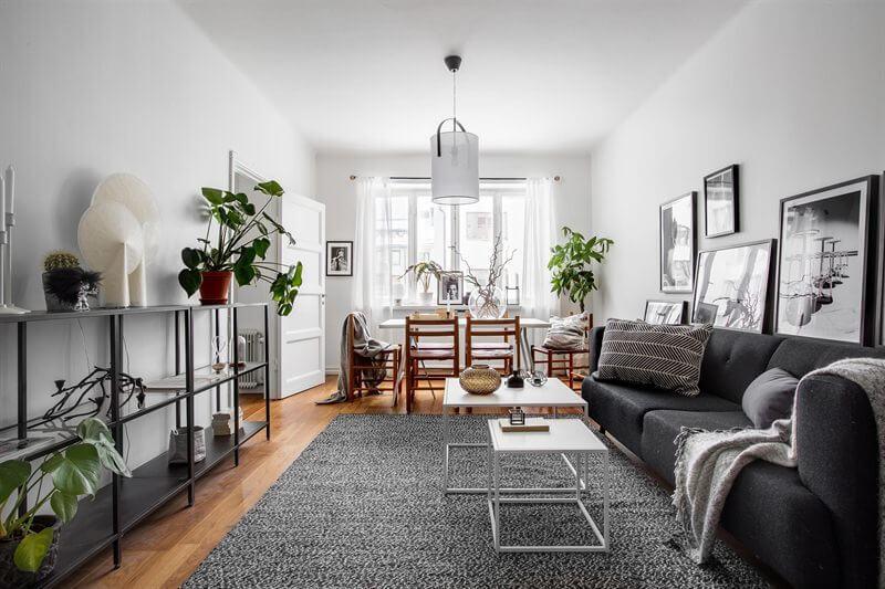 フローリングはライトブラウンからミディアムブラウン位の色でソファーはダークグレイ。ラグマットはライトグレーでリビングテーブルは小さめのものでホワイトです。壁に写真を飾っていてモノトーンで統一されています。背の低い家具で統一されています。オープンラックは圧迫感を感じませんね。