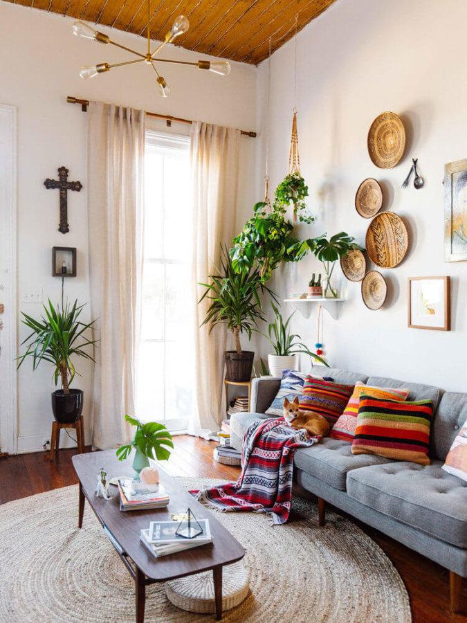 壁は、ザンビアとジンバブエに根ざした美しい、手織りのトンガバスケットが設置フローリングの色はミディアムブラウンからダークブラウンの中間位でしょうか。ソファーはライトグレーで置いてあるクッションがとても個性的です。壁に飾っているものもエスニックなものが多くもしかしたら旅行が好きな人なのかもしれません。全体的に丸みのあるデザインを多用していてナチュラルな印象です。