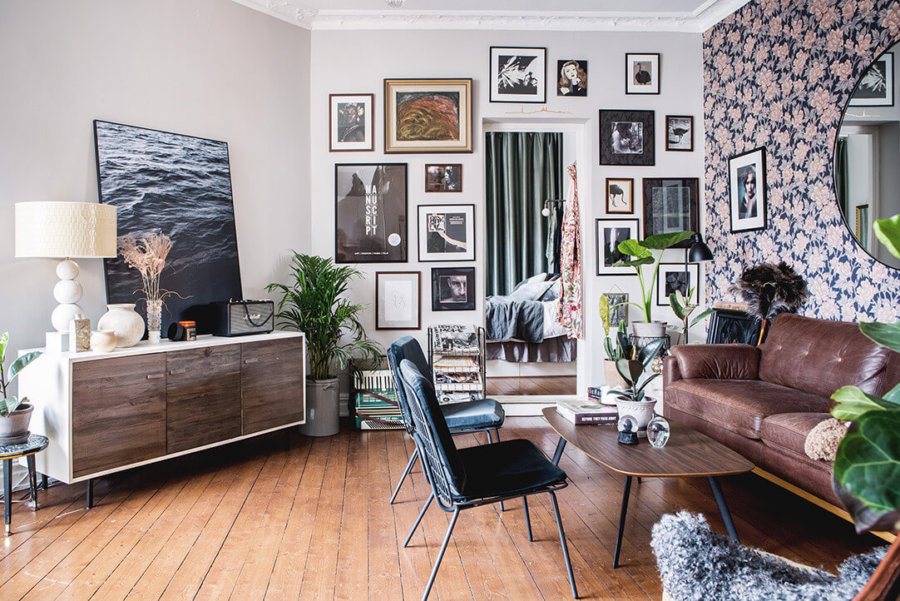 個性的な壁紙ですね。ソファーはブラウンレザーを使用しています。絵や写真をランダムに貼り付けています。3人掛けソファーとリビングチェアを2つ置くのがオーソドックスなスタイルのようです。