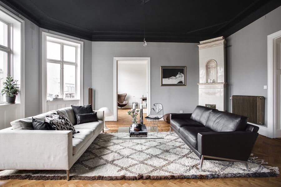 明るい床でヘリンボーン柄のフローリングでしつらえています。白いソファーとブラックのソファーを1台ずつ置いています。ガラスのリビングテーブルがどちらにもつかない感じがいいですね。床が明るい色のフローリングを使用した部屋のおしゃれなインテリア実例集