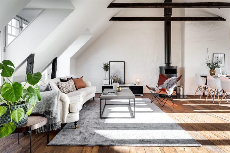 床が古材でソファが白、黒い暖炉あり海外のインテリア事例