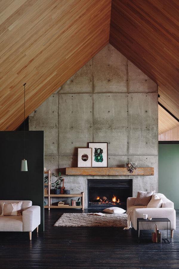 ブラックに近いダークブラウンからのフローリングにホワイトのソファーとアイボリーのラグマットを敷いています。壁面が一面だけコンクリートを使用していてその下に暖炉が埋め込んであります。三角屋根になっていて屋根はナチュラルブラウンからの屋根になっています。屋根の色が明るいことで空間は圧迫感を感じません。