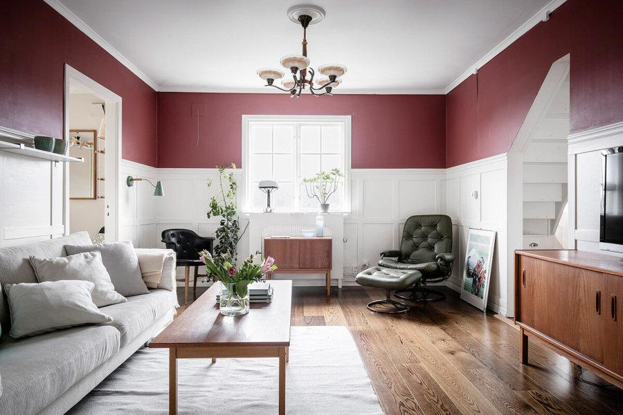 フローリングはミディアムから出ソファーはアイボリーです。木製家具をフローリングの色と揃えています。統一感をそこでしっかり出しておきながら壁面の色で小豆色を使ってアクセントにしています。