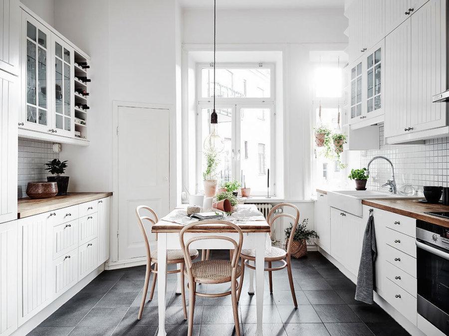 ダークグレーのタイルにホワイトのキッチンです。日本でもホワイトのキッチンは主流になっていますがキッチンカウンターの天板を木材にすることで北欧風のイメージになります。キッチンとダイニングテーブルが統一されています。全体的に明るい中に昨日の曇りを感じさせることができます。窓際に観葉植物置いてあるのもいいですね。
