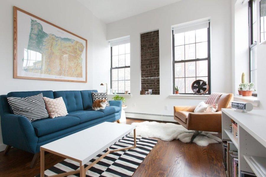 フローリングはミディアムブラウンでソファーはブルーです。リビングチェアはブラウンレザーを使用しています。窓と窓の間がコンクリートになっている変わったインテリアです。木製家具はホワイトにして圧迫感を感じないように工夫されています。