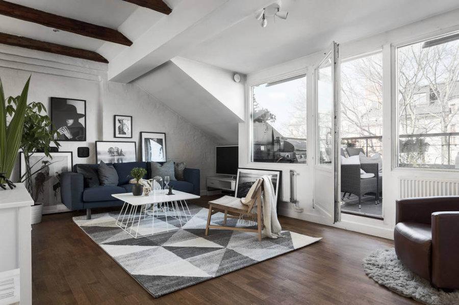 フローリングの色はダークブラウンからだからミディアムブラウンからの中間位です。建具壁面を全てホワイトで統一されていてソファーはネイビーを使用しています。リビングテーブルは正方形のホワイトを使用していてラグマットでグレイでアクセントになっています。リビングチェアはナチュラル系の木目でバランスを整えています。壁に飾ってある家はモノトーンで統一されています。