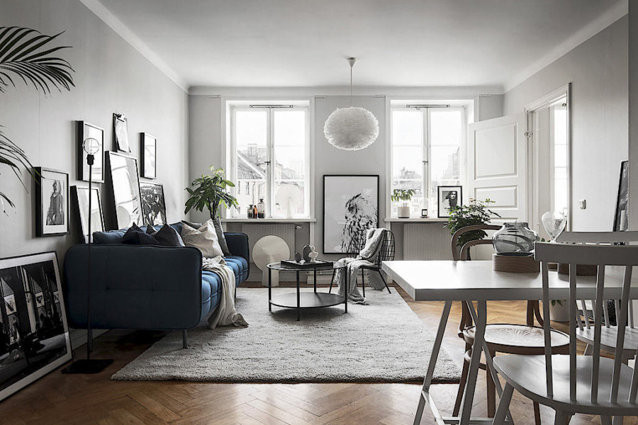 フローリングはヘリンボーンでナチュラルカラーで色はやや濃い色です。ソファーの色はネイビーにすることで空間の中で主役として存在しています。モノトーンの絵をたくさん飾って統一感を出しています。ダイニングテーブルはホワイトです。