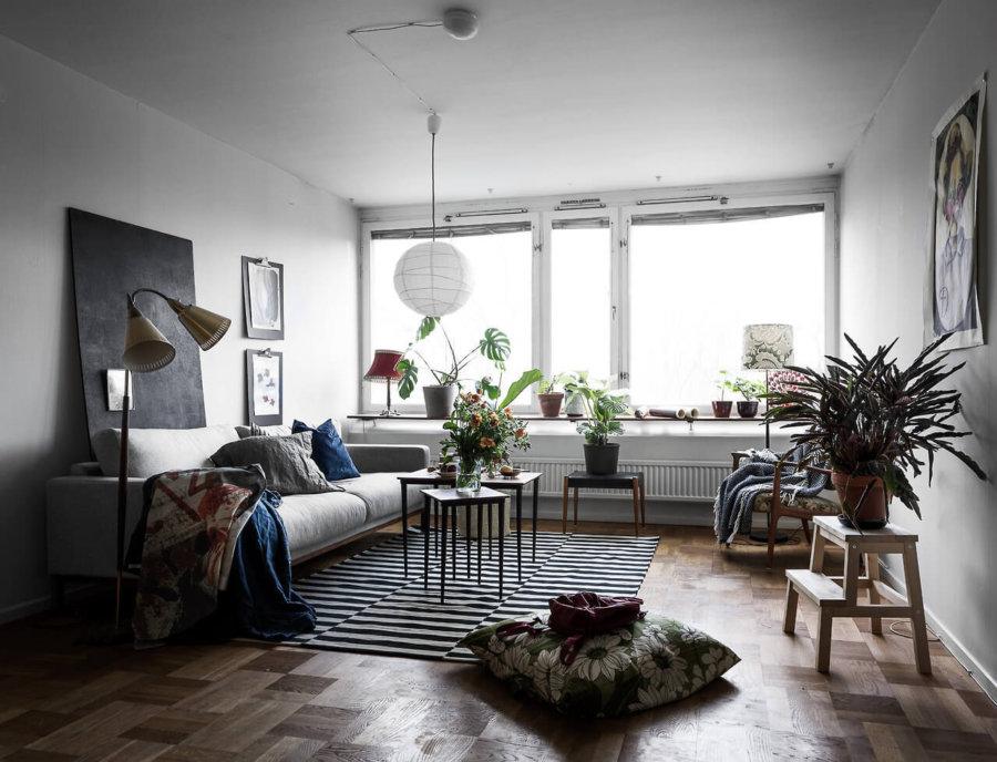 ライトグレーのソファーを置いています。クッションやスローがブルーでアクセントになっています。ラグマットのデザインも個性的ですね。観葉植物をたくさん置いていて全体にナチュラルな雰囲気が漂っています。