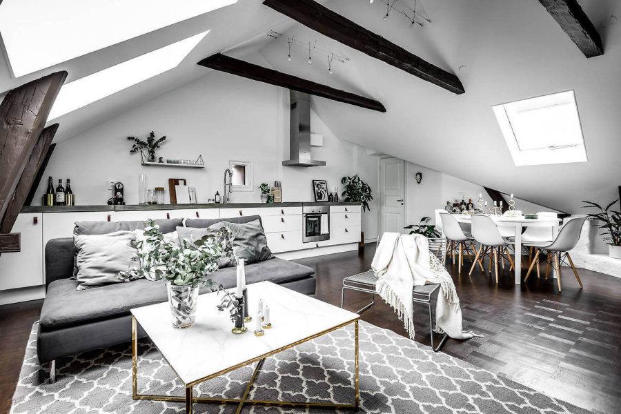 屋根裏部屋を改造しており天井は勾配天井になっています。フローリングの色はダークブラウンからです。ソファーはグレーでラグマットはライトグレーになっています。シェルチェアーはホワイトで合わせていてダイニングテーブルもホワイトです。白からグレーのグラデーションの中でカラーコーディネートされています。