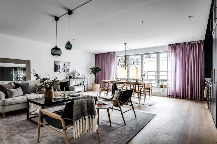 紫色のカーテンと明るい床のフローリングでインテリアをコーディネートしています。ダイニングテーブルはライトブラウンからです。窓からたくさんの光が入ります。窓際にダイニングを持ってくるのは珍しいですね。