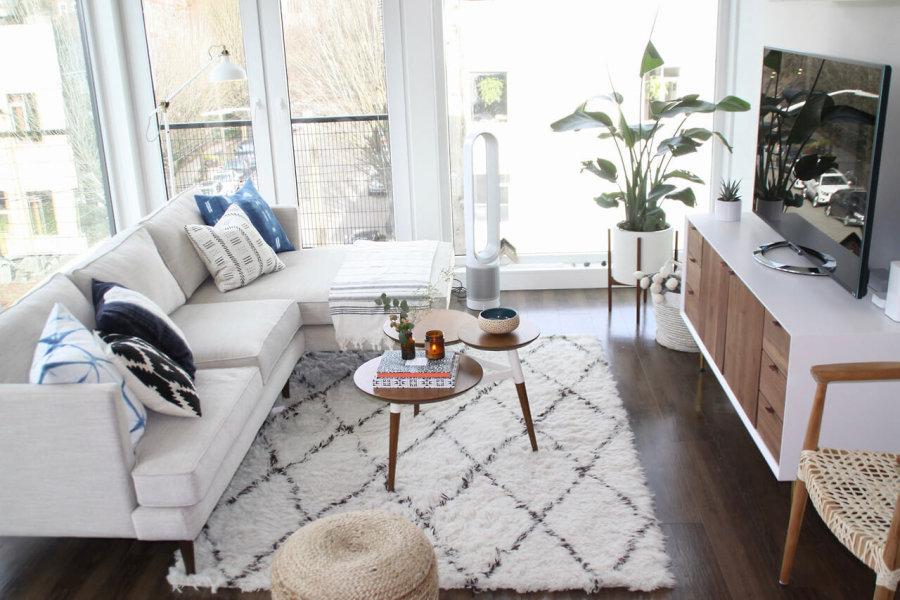 ダークブラウンからのフローリングにホワイトのソファーとホワイトのラグマットを敷いています。テレビボードはフレームがホワイトで全面はウォールナットを使用しています。2色使うことで家具の存在感を抑えています。おそらくあまり広い部屋ではないでしょうけれどもホワイトを上手に使っているので圧迫感を感じさせません。観葉植物の鉢もホワイトで揃えています。