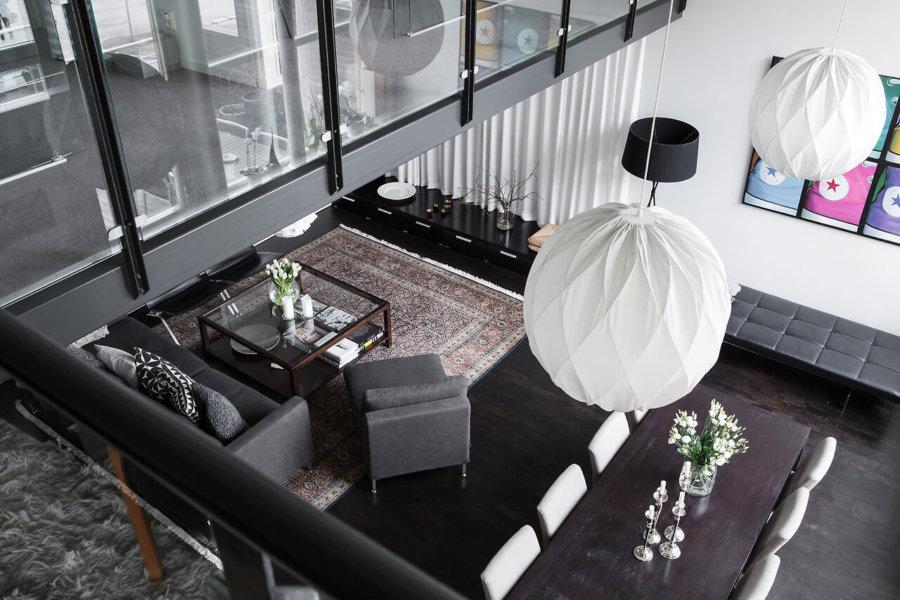 床の色と家具がブラックで北欧系の照明がアクセントになっている海外事例