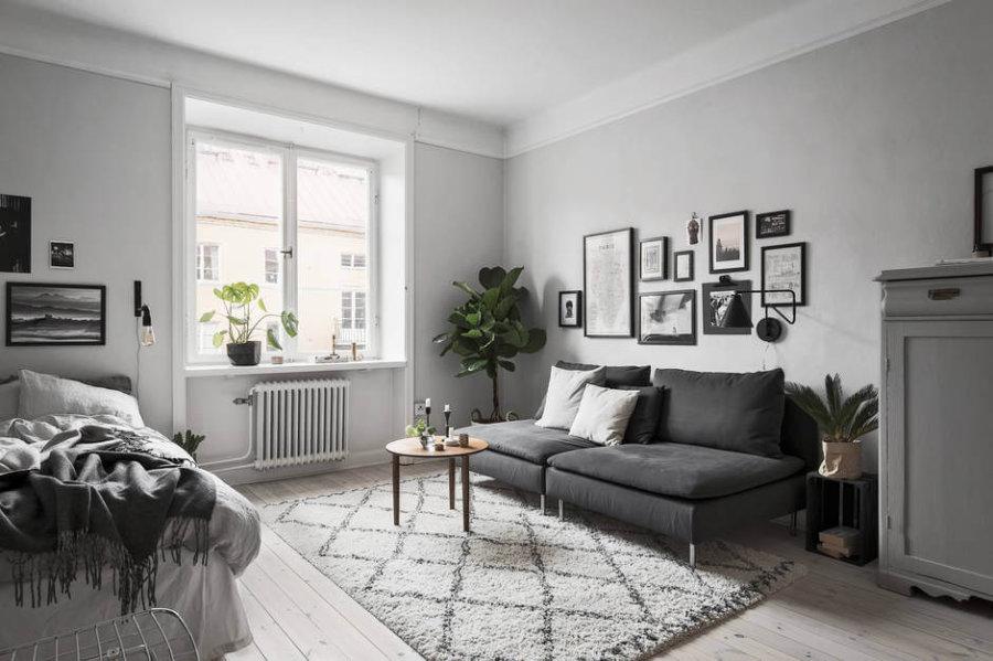 ホワイトのフローリングにホワイトの壁面でダークグレーのソファーをポイントにしています。ソファーの前のリビングテーブルは丸い木目調のものを使用しています。部屋はあまり狭く見せたくないのでそうしていると思われます。