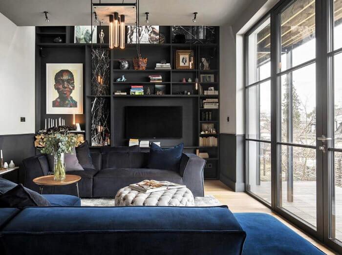 明るいフローリングに壁面収納がブラックで統一されています。ソファーはネイビーで空間を引き締めています。窓が大きいので光が十分に入り込み暗い印象はありません。ブラックの収納家具はほこりが目立つので掃除が大変そうです。本当に好きな人じゃないと難しいかもしれませんね。