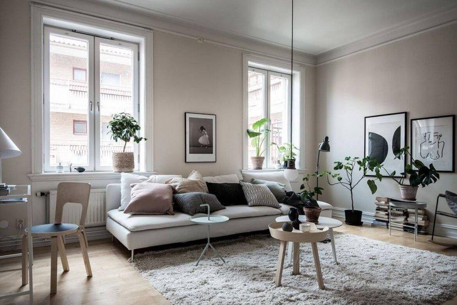 明るいフローリングで白いソファーを配置しています。クッションがたくさん置かれていておしゃれですね。観葉植物も小さめのものをたくさん置いています。リビングテーブルは小さい。テーブルを数多く置いていて圧迫感を感じません。