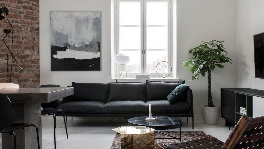 ホワイトの床にブラックのソファーを配置しています。画像の左側にレンガが見えるので空間全体ではアクセントになっていると思われます。