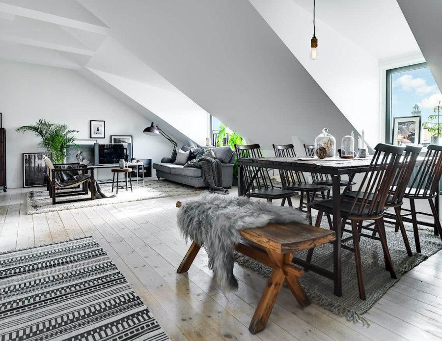 白に近い色のフローリングに天井は勾配天井です。アパートの最上階だと思われます。光をたくさん入るので空間は非常に明るいです。ソファーはライトグレーでダイニングセットは古い木材を使用しておりヴィンテージ感があります。