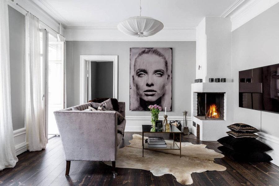フローリングの色はダークブラウンカラーで1枚1枚のフローリングの板に色のブレがあります。テレビは壁掛けテレビを使用しています。ソファーはグレーがかったアンティーク調のソファーを配置しています。部屋の角には暖炉があり全体的にはモダンな印象です。