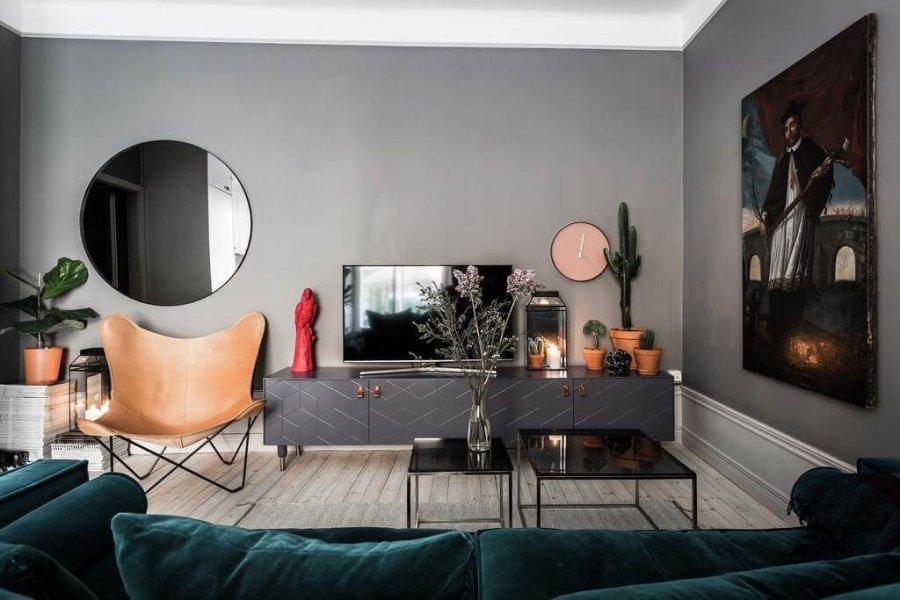 ブラックのテレビボードとキャメルのバタフライチェアーをグレーの床にコーディネートした海外インテリ事例。